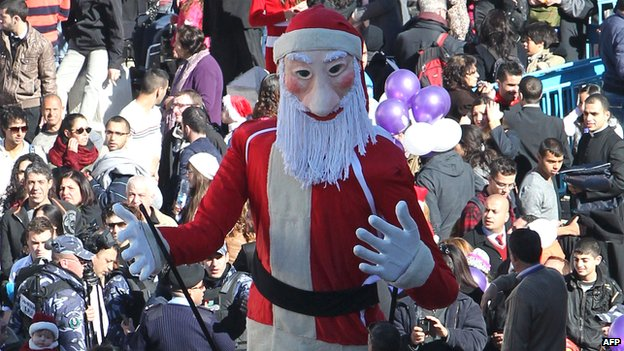Christian pilgrims gather near a Santa Claus dummy at Manger Square in Bethlehem