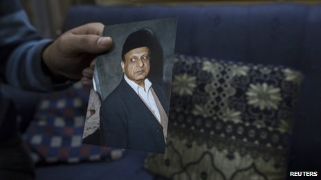 A photograph of Masood Ahmad is held by his nephew at his house in Lahore December 10, 2013