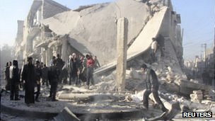 Syrians inspect a damaged building