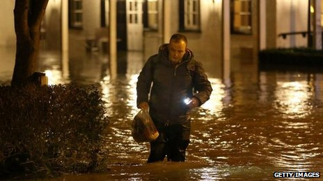 Man wades through rising floodwater from the River Mole outside the Burford Bridge Hotel near Dorking on December 24 2013