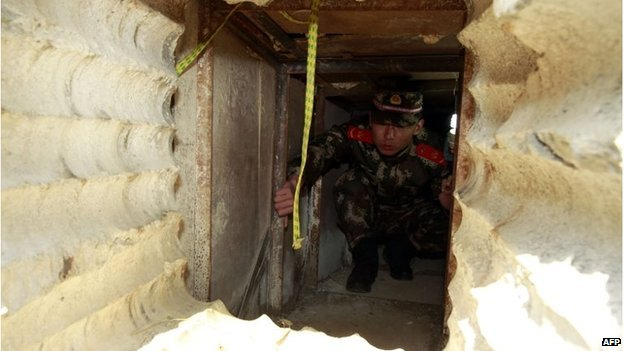 This picture taken on December 24, 2013 shows a soldier checking an underground tunnel leading to Hong Kong from Shenzhen