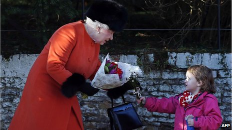 The Queen receives a bunch of flowers from a child after the service