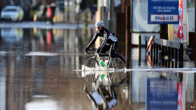 A cyclist riding through deep flood water
