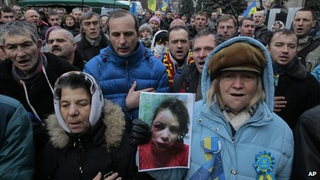 Activists hold the photo of journalist and activist Tetyana Chornovol as they rally outside the Ukrainian Interior Ministry in Kiev on 25 December, 2013