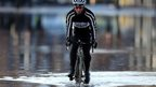 Cyclist riding through flood water