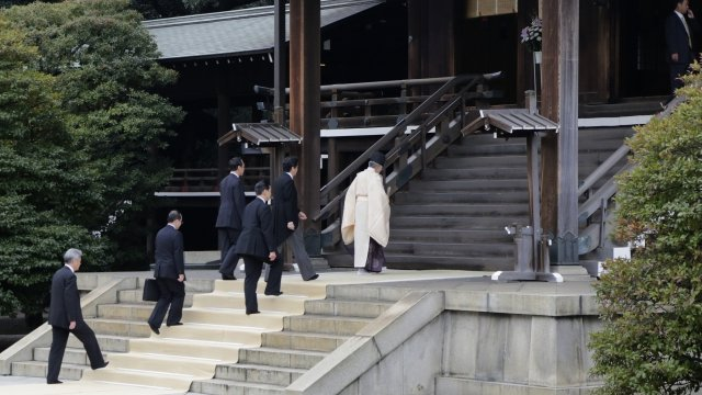 Japanese PM Shinzo Abe follows priest up steps of shrine