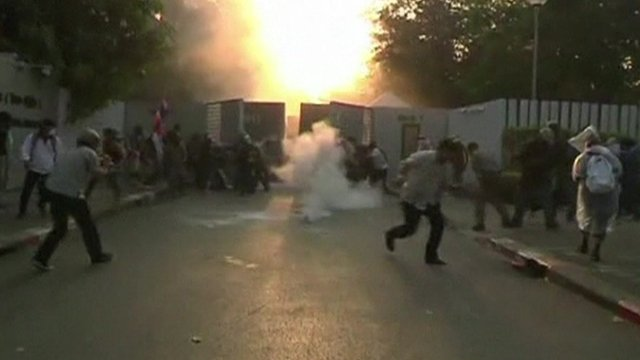 Tear gas grenade exploding in among fleeing protesters