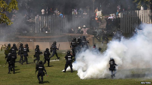 Riot policemen run after anti-government protesters trying to enter the Thai-Japan youth stadium in central Bangkok