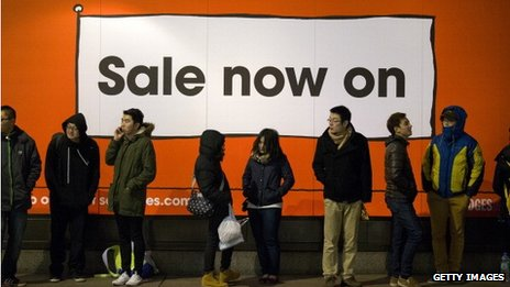 A queue of people outside a Sale sign in London