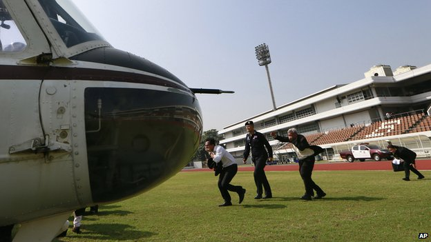 Thai election commission officials are escorted by a policeman to a helicopter during an evacuation after the registration was disrupted by anti-government protesters at a sport stadium in Bangkok