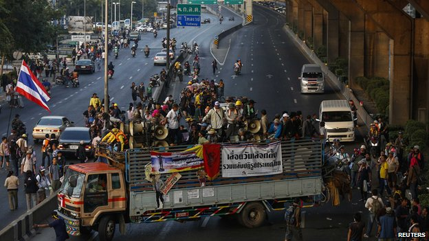 Anti-government protesters gather as they block Vibhavadi Rangsit road after clashes with riot police in central Bangkok