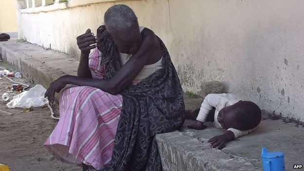 A South Sudanese woman with a child sits at the main hospital in Bor which troops loyal to President Salva Kiir re-captured from rebel forces on 25 December, 2013