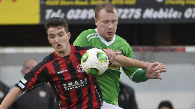 Joshua Robinson of Crusaders in action against Cliftonville striker Liam Boyce