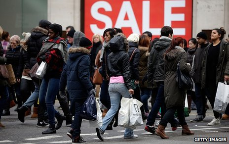 "Shoppers pass in front of a large ""sale"" sign"