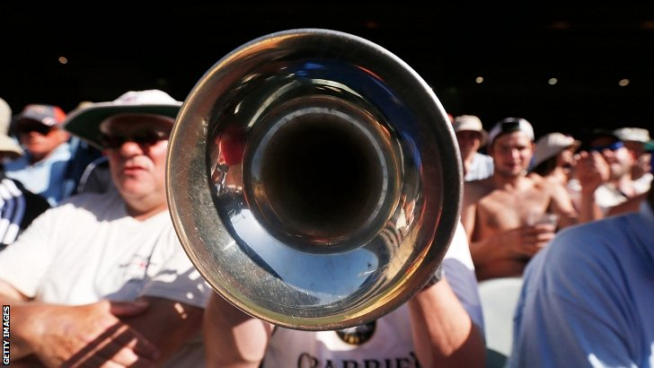The Barmy Army trumpeter plays during day two