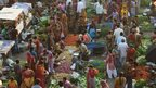 Customers shop for vegetables at a market in Ahmedabad on October 22, 2013