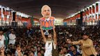 A supporter of the Bharatiya Janata Party(BJP) holds a cutout of Gujarat state Chief Minister and the Bharatiya Janata Party's (BJP) prime ministerial candidate Narendra Modi during an election rally in New Delhi