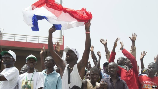 A Malian man holds a French flag and cheers as he listens to the French President make a speech during the inauguration celebration of Mali's new president at the March 26 stadium in Bamako, sept 2013