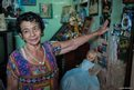 An elderly lady points towards a portrait of revolutionary, Camilo Cienfuegos