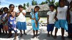 Students from Uekera Primary School pose with the Queen's Baton in Tarawa, Kiribati.