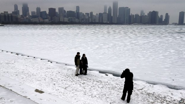 People take photos by Lake Michigan in Chicago, on 25 December 2013