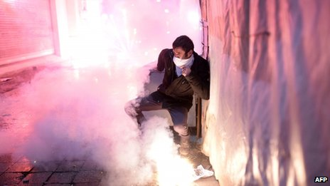 A Turkish protestor protects himself as fireworks explode on the Istiklal Avenue on December 27, 2013, during clashes between the Turkish police and protestors