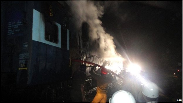 Indian rescue personnel attempt douse smoke in a burning carriage of the train.