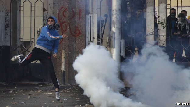 A student of Al Azhar University throws a stone during clashes with riot police and residents of the area at the Al Azhar University campus in Cairo, 27 December 2013