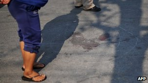 Thai anti-government protesters stand near a bloodstain on the road outside Government House in Bangkok on Saturday, after a fellow protester was shot dead by an unknown gunman