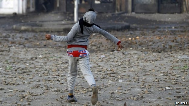 A supporter of the army and police throws a stone during clashes with students of Al Azhar University, Cairo, Egypt, 27 December 2013
