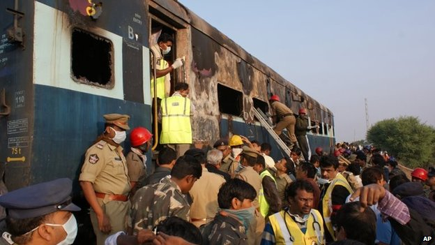 Policeman and firefighters search for victims of a train accident at Kothacheruvu, Andhra Pradesh state, India, on Saturday