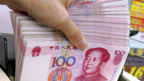 A teller counts Chinese yuan notes