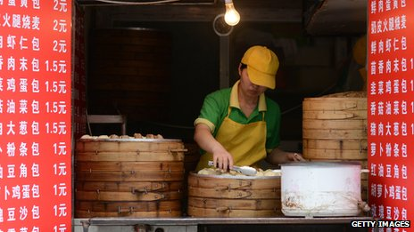 A vendor waits for customers in a steamed stuffed-bun stall in Beijing on May 9, 2013