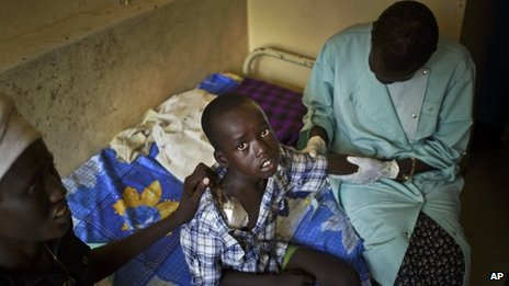 A child is examined by two doctors at the Juba Military Hospital