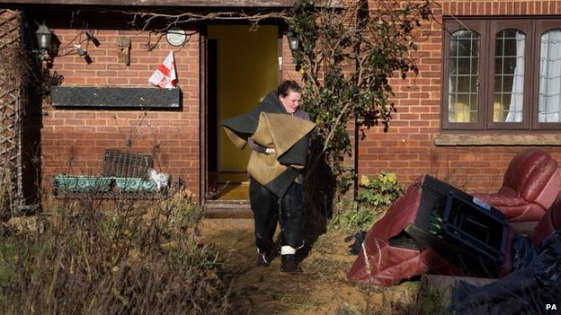 A woman carries dripping carpet from her home in Yalding, Kent, after it was flooded during the recent bad weather