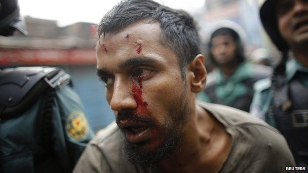 Police detain an injured man they suspect of being an activist of the banned Islamist organization Hizb-ut-Tahrir, in Dhaka December 27, 2013