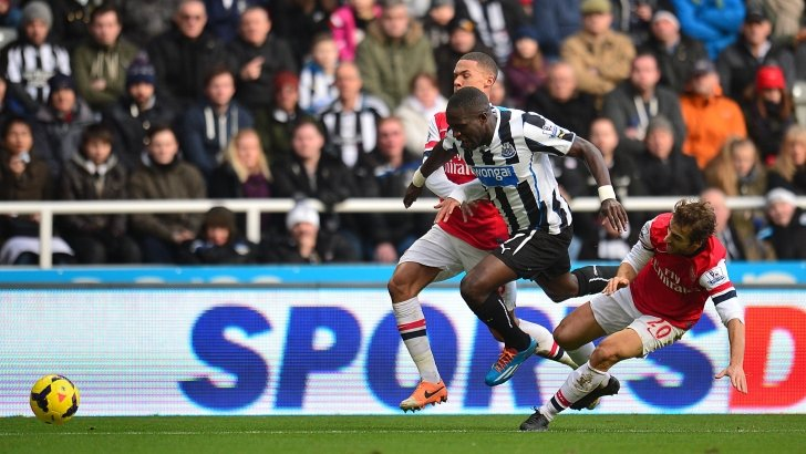 Newcastle United's Moussa Sissoko goes down under a challenge from Kieran Gibbs and Mathieu Flamini