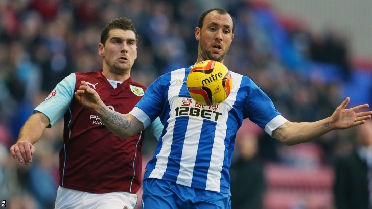 Wigan Athletic's Ivan Ramis (right) controls the ball under pressure from Burnley's Sam Vokes