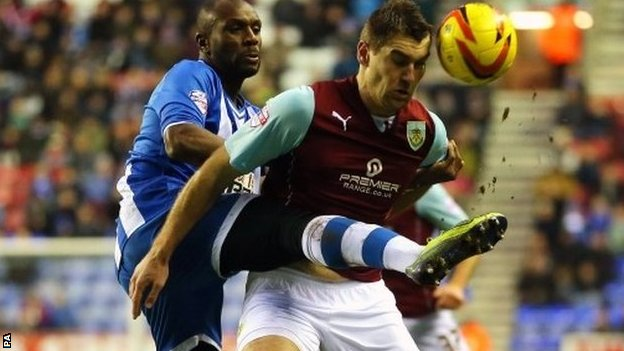 Wigan Athletic's Emerson Boyce challenges Burnley's Sam Vokes