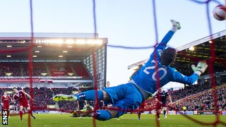 Ross County goalkeeper Michael Fraser saves Scott Vernon's penalty