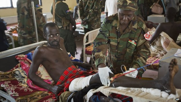 A patient being treated by a military doctor in a ward of mainly soldiers with gunshot wounds, Juba Military Hospital, South Sudan