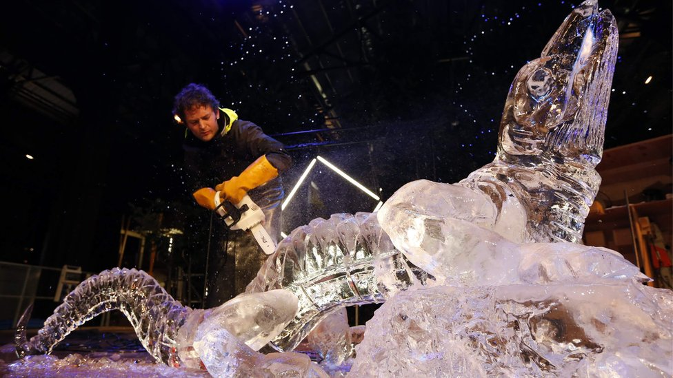 An artist uses a chain saw to create an ice sculpture in the form of a lizard