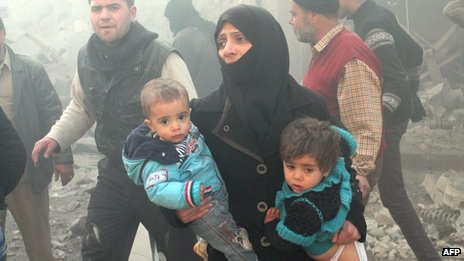 A Syrian woman carries children after airstrikes in Aleppo