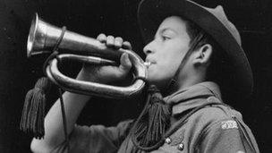 A boy scout sounds the alarm on a bugle.