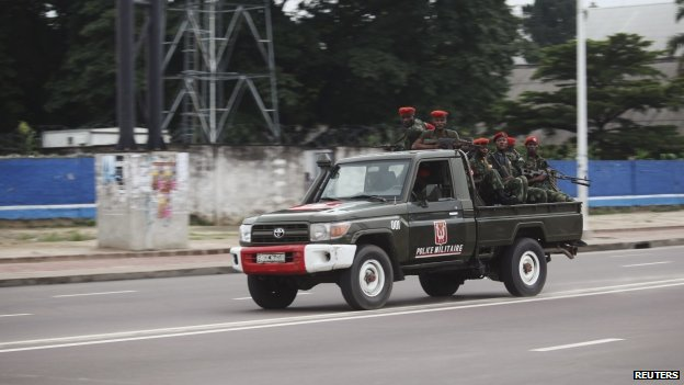 Congolese soldiers ride on their pick-up truck towards the state television headquarters in the capital Kinshasa, 30 December 2013
