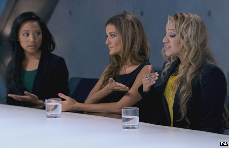 Three Apprentice candidates are in the boardroom, two seemingly bickering with each other
