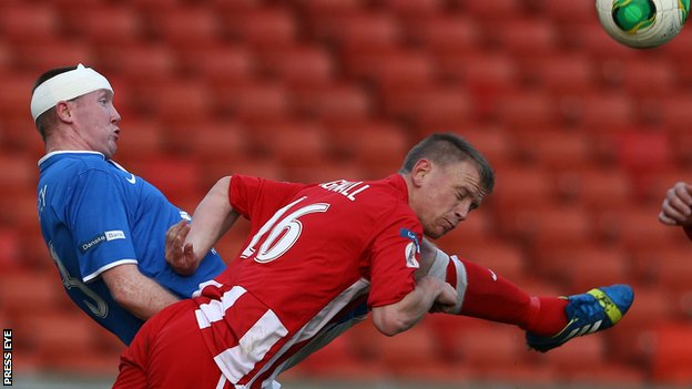 Linfield defender Kyle McVey challenges Warrenpoint's Liam Bagnall