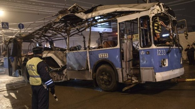 A policeman watches as a bus, destroyed in an apparent suicide attack earlier on Monday, is towed away in Volgograd