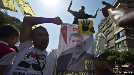 Supporters of ousted Egyptian president Mohamed Morsi shows Morsi's portrait and posters with the four finger symbol during a demonstration against the military backed government on September 13, 2013 in the Egyptian capital, Cairo.