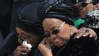 Winnie Madikizela-Mandela (L), ex-wife of former South African President Nelson Mandela, and Graca Machel, widow of Mandela, react as his flag-draped coffin arrives at the Mthatha airport in the Eastern Cape province - 14 December 2013